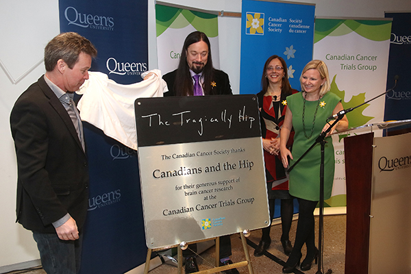 Gord Sinclair and Rob Baker of The Tragically Hip unveil a plaque honouring the band as Janet Dancey, Director of the Canadian Cancer Trials Group, and Lynne Hudson, President and CEO of the Canadian Cancer Society, look on. (Photo by Bernard Clark)