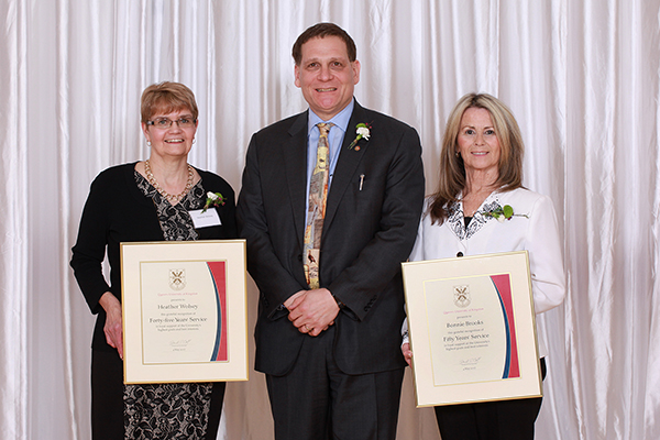 Principal Daniel Woolf presented certificates to faculty and staff members marking milestone years, including Heather Wolsey, left, for 45 years, and Bonnie Brooks, who has worked at Queen's for 50 years. (Photo by Bernard Clark)
