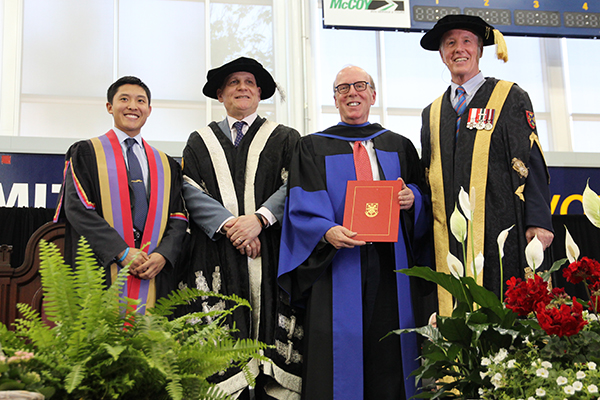 Stephen J.R. Smith holds up his honorary degree from Queen's University during Tuesday's Spring Convocation ceremony at the ARC, with Rector Cam Yung, Principal Daniel Woolf, and Chancellor Jim Leech.