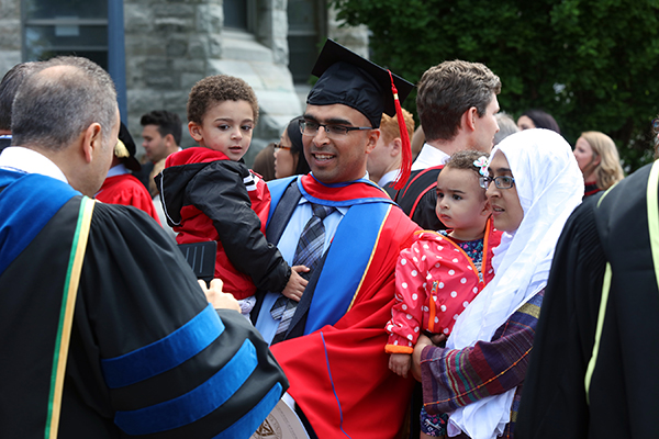 A doctoral graduate takes some time with his family after receiving his PhD from Queen's during Spring Convocation. (Photo by Bernard Clark)