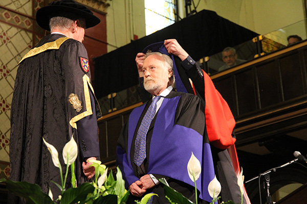 Otto Naumann is hooded by Interim Dean of the Faculty of Arts and Science Gordon Smith as Chancellor Jim Leech looks on during Tuesday morning's convocation ceremony at Grant Hall.