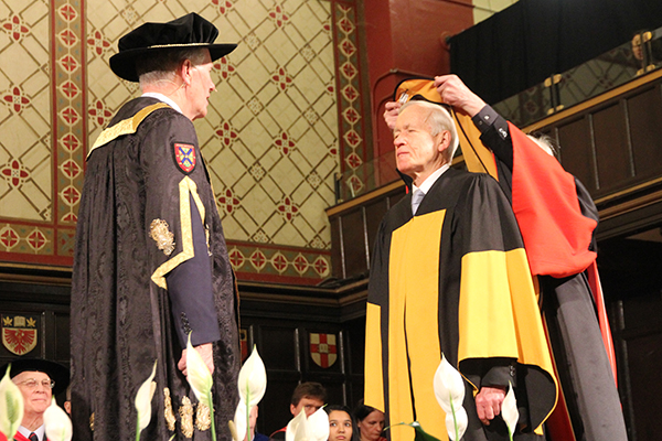 Interim Dean in the Faculty of Arts and Science Gordon Smith hoods Sir David Skegg as Chancellor Jim Leech looks on during Friday's Spring Convocation ceremony at Grant Hall.