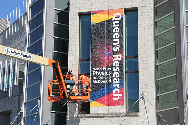 A building banner celebrating the achievements of researchers at Queen's University is installed on the front facing of Joseph S. Stauffer Library.