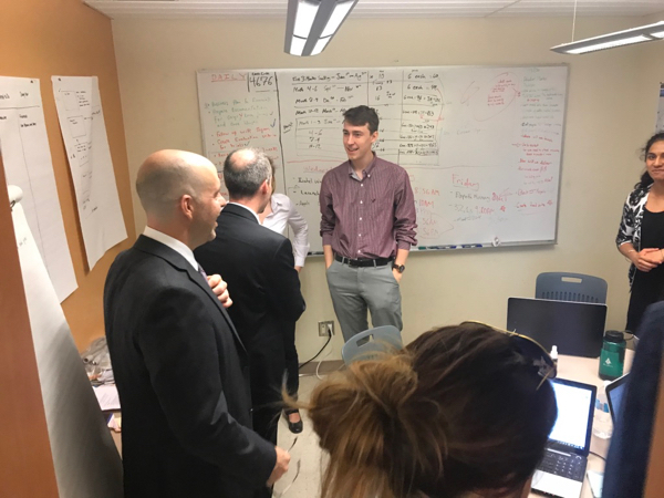 Mayor Bryan Paterson speaks with a QICSI student team regarding their start-up, during his tour of innovative research and development groups at Queen's.