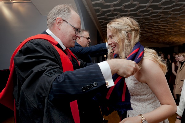 Dr. Hugh Horton presents a new BISC student with her scarf. (Supplied Photo)