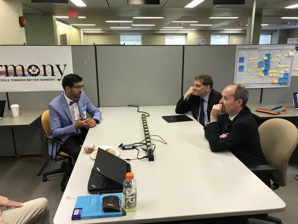 Mayor Bryan Paterson and Principal Daniel Woolf speak with Shahram Yousefi, co-founder of Canarmony and the acting head of the Department of Electrical and Computer Engineering.