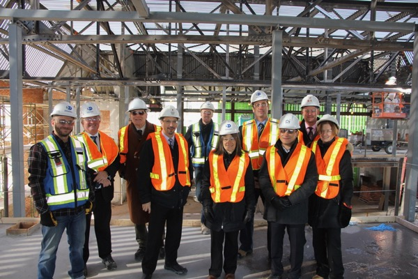Jim McLellan (Academic Director, DDQIC), Principal Daniel Woolf, Kevin Deluzio (Dean, Faculty of Engineering and Applied Science), MPP Sophie Kiwala, MP Mark Gerretsen, Franco Lora (IWC project manager) John Witjes (Associate Vice-Principal Facilities), and Ann Tierney (Vice-Provost and Dean, Student Affairs) meet with workers from Ellis Don Construction (blue vests) during a tour of the Innovation and Wellness Centre.