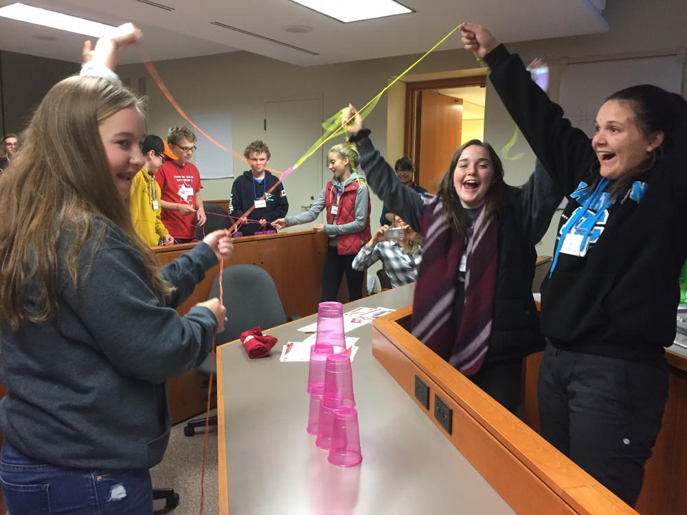 Ninth grade students of Queen's staff play a game to stack pyramids of cups using only string. (Photo by Carla Ferreira Rodrigues)