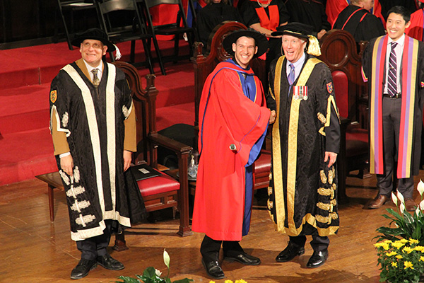A PhD recipient looks for his family as he shakes hands with Chancellor Jim Leech, while Principal Daniel Woolf and Rector Cam Yung look on.