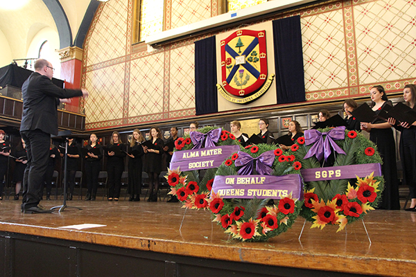 Darrell Bryan (Music) leads the Queen's Choral Ensemble as they perform at the Remembrance Day service on Friday at Grant Hall. (University Communications)