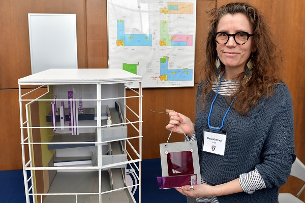 Ms. Claus showcases her proposal at Monday's open house. It consists of wampum belts made of translucent purple coloured and frosted clear acrylic sheets and hung vertically from the ceiling. (University Communications)