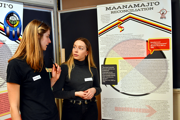 "Penny Cornwall (Artsci'18) speaks with Madeline Heinke (Artsci'18) in front of their team's exhibit, Maanamaji'o. The word means ""the community (or the person) is sick."" (University Communications)"