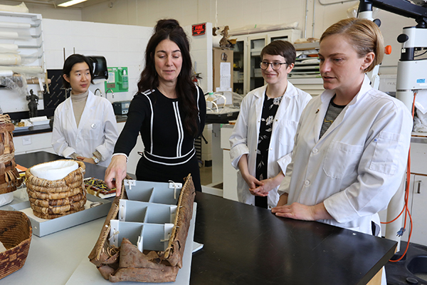 Art conservation professor and students work to restore baskets.