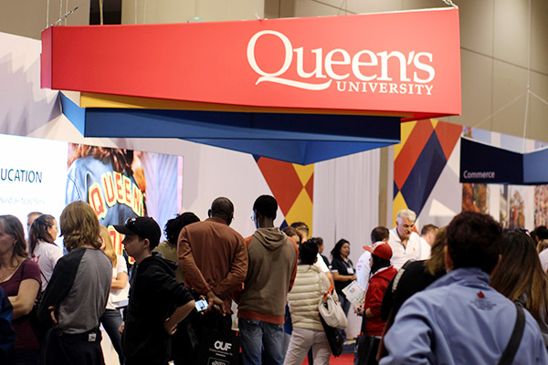 Prospective students and their families visit the Queen's University booth at the Ontario Universities' Fair