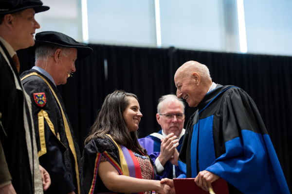Honorary degree recipient Gerald Sutton (Com'48) shakes the hand of Rector Alex Da Silva during the convocation ceremony for the Smith School of Business Commerce program on June 11, 2019. (Queen's University/Garrett Elliott)