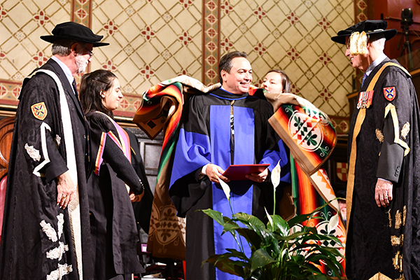 Perry Bellegarde, National Chief of the Assembly of First Nations, receives a blanket after Queen's conferred an honorary degree upon him at Fall Convocation.