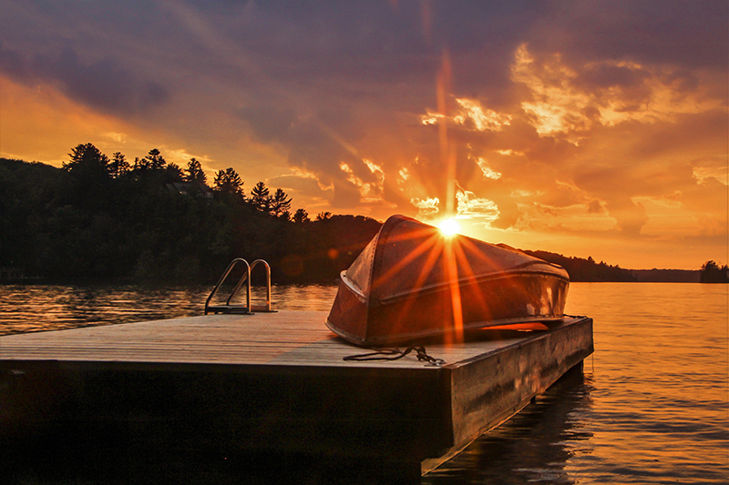 Photo of an aluminum boat upside down on a dock in front of a sunset.