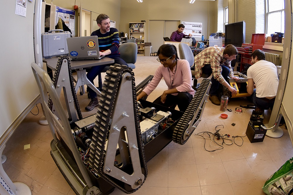 [A group of researchers collaborating in a space with mobile robots]