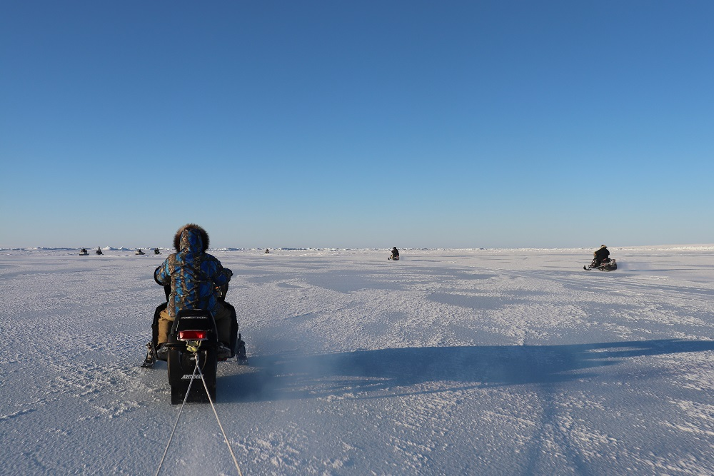 [Researchers and community members travelling on snowmobiles]