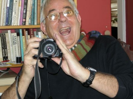 Image of Geoff Smith smiling with a camera