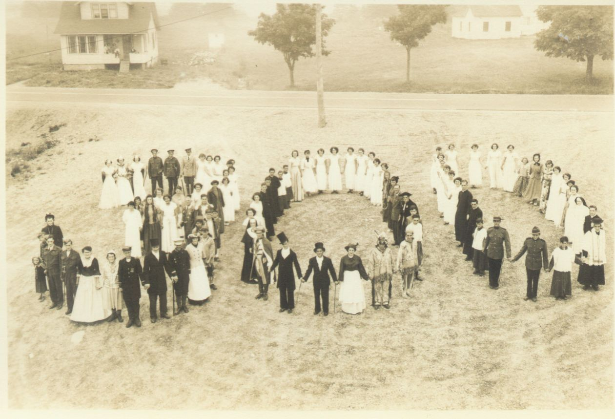 Photo of a large group of Acadian men and women dressed in traditional costume, standing in a empty lot forming the number 300, taken in 1951 from Pubnico, Nova Scotia