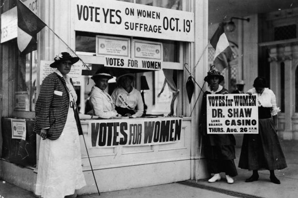 Image of a group of women at a booth fighting for women suffrage