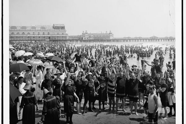 Image of a photo of a crowded beach on Coney Island around the turn of the century.
