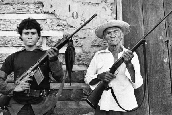 Image of two generations of Latin-American men holding firearms