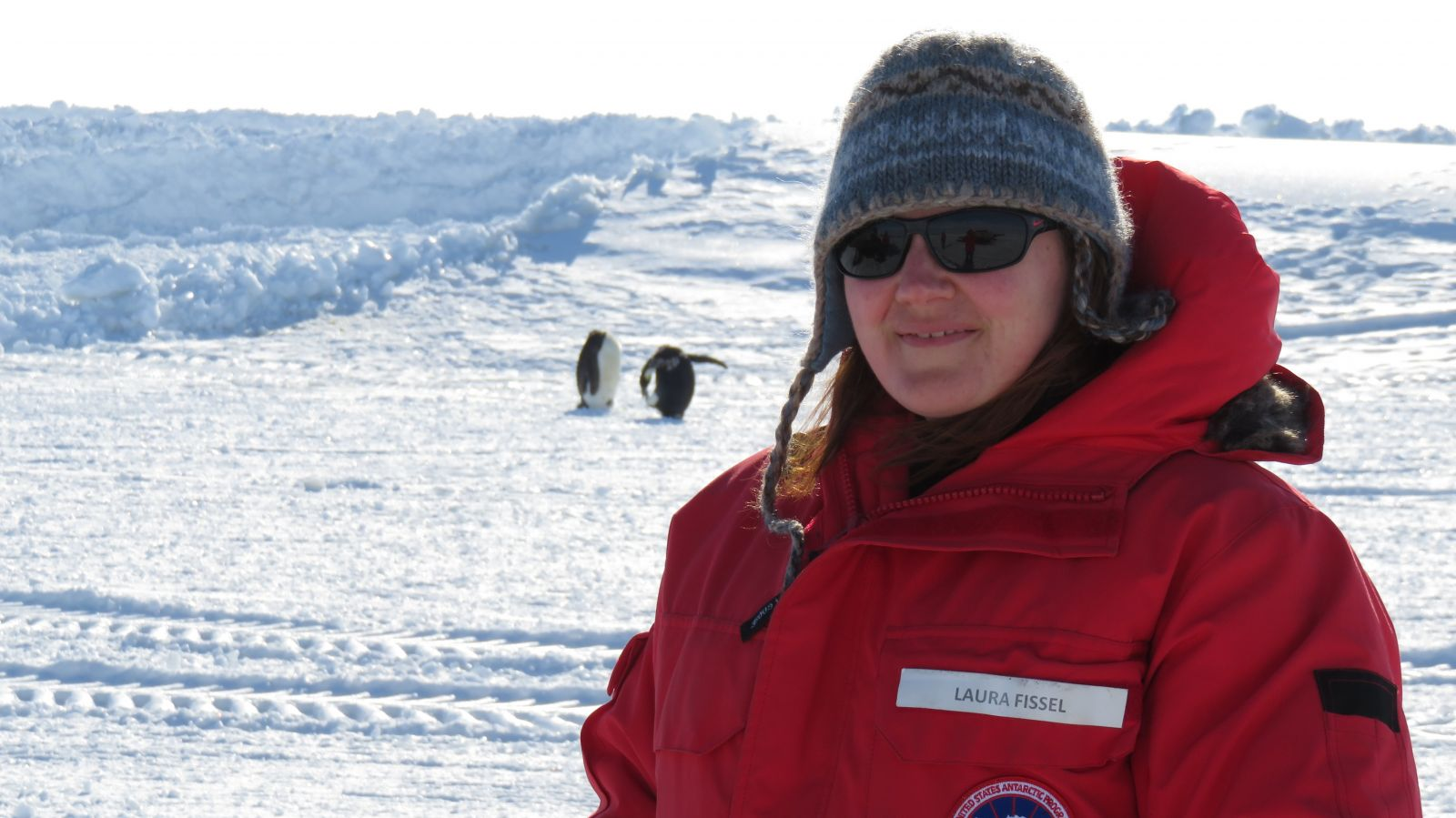 Laura Fissel at Pheonix Airfield, Antarctica with two emperor penguins in the background.