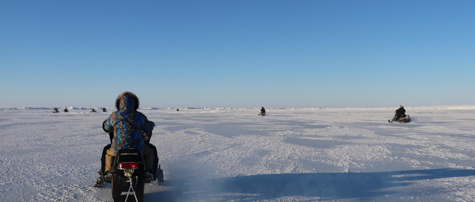 [Researchers and community members travelling on snowmobiles to Ulukhaktok]