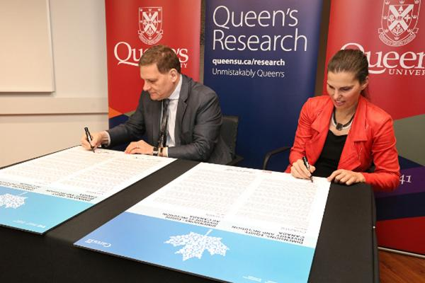 [Queen's Principal and Vice-Chancellor, Daniel Woolf, and Minister of Science and Sport, Kirsty Duncan, sign the Dimensions EDI charter.]