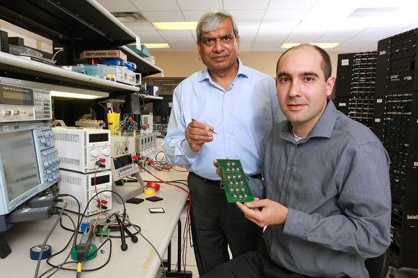 [Photo of Praveen Jain and Marko Krstic at the ePOWER lab at Queen's.]