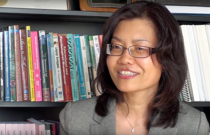 Liying Cheng in front of book shelf.
