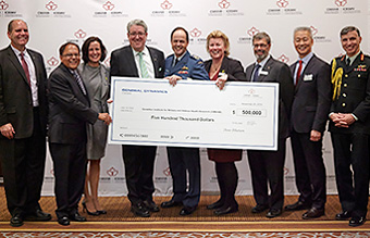 [photo: General Dynamics cheque presentation]