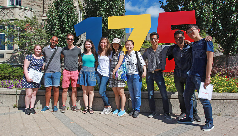 [International students in front of the Queen's 175 sign]