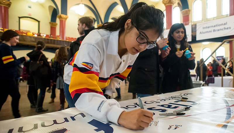 [student signing banner]