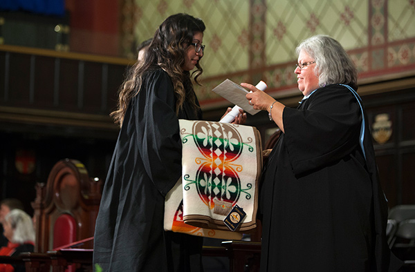 [Aboriginal student presented with traditional blanket at convocation]