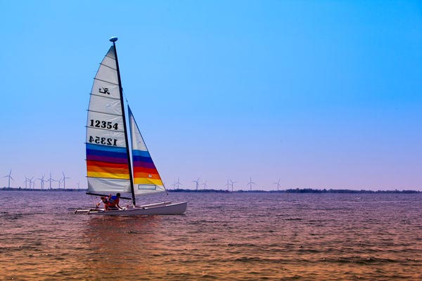 [photo of people sailing by the Kingston Yacht Club]