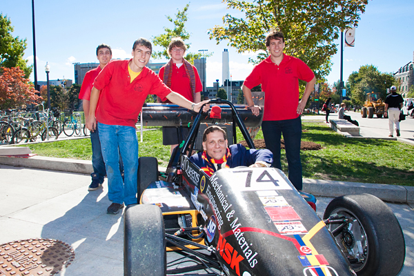 [Daniel Woolf in a car being developed by Queen's Formula SAE Team]