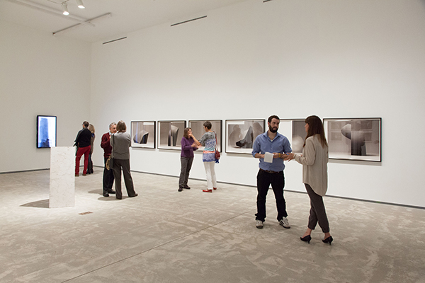 [Brooklyn-based artist Erin Shirreff (far right) speaks to a Queen's Journal reporter in the gallery]