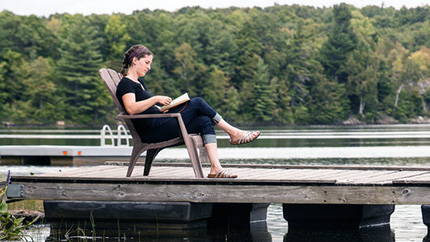 [student reading on a dock]
