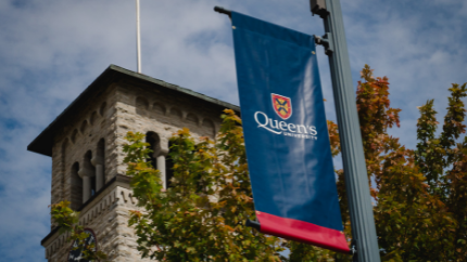 Image of Grant Hall with a blue pole pennant in front of it, pennant has Queen's logo.