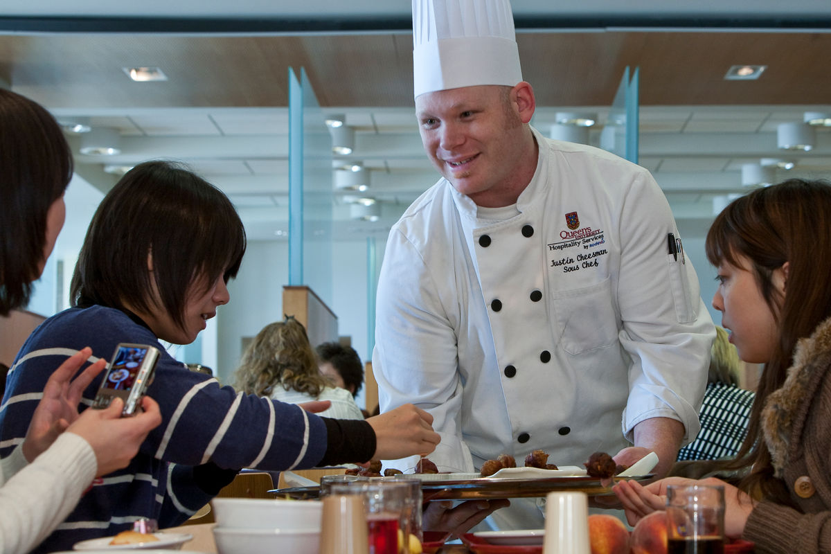 Students sampling from Sous Chef Justin Cheesman at Doors Open Queen's at Leonard Hall